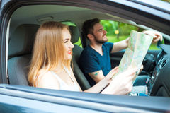 Couple of young people traveling. Couple spending weekend on nature. Searching road to go. Traveling by a car Royalty Free Stock Photo