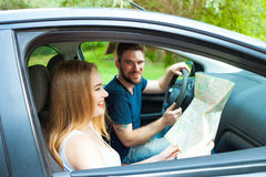 Couple of young people traveling. Couple spending weekend on nature. Searching road to go. Traveling by a car Stock Photo