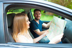 Couple of young people traveling. Couple spending weekend on nature. Searching road to go. Traveking by a car Royalty Free Stock Images
