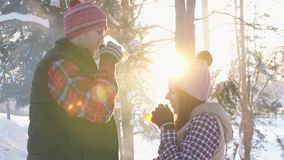 Couple of young people in winter clothes drinking hot mulled wine at sunset in winter forest, winter vacation slow mo. Couple of young people in winter clothes stock video footage