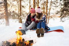 Couple of young people in the winter by the fire Royalty Free Stock Photo