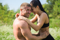 Couple of young sportsmen hug and kiss outdoors after workout Stock Photo