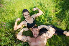 Couple of young sportsmen lie on green grass after workout outdoors Stock Image