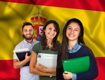 Young students over spanish flag. Couple of young students with books over spanish flag Stock Images