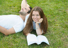 Couple of young students reading books together in the park Royalty Free Stock Image