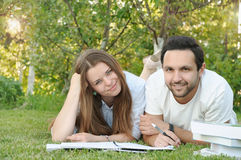Couple of young students studing in the park by the campus Stock Photo