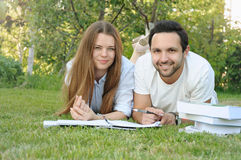 Couple of young students studying in the park by the campus Stock Photos