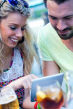Couple of young students using a digital tablet in the bar. Stock Photography