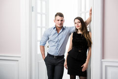 Couple of  young stylish people in the doorway home interior loft office. Stylish men in a shirt and a girl in an evening black dress Royalty Free Stock Images