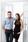 Couple of  young stylish people in the doorway home interior loft office. Stylish men in a shirt and a girl in an evening black dress Stock Images