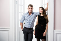 Couple of  young stylish people in the doorway home interior loft office. Stylish men in a shirt and a girl in an evening black dress Royalty Free Stock Photography