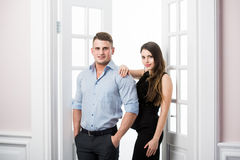 Couple of  young stylish people in the doorway home interior loft office. Stylish men in a suit and a girl in an evening black dress Stock Photo
