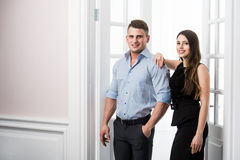Couple of  young stylish people in the doorway home interior loft office. Stylish men in a suit and a girl in an evening black dress Royalty Free Stock Image