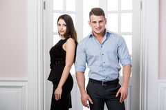 Couple of  young stylish people in the doorway home interior loft office standing back to each other Royalty Free Stock Photography