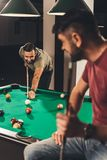 Couple of young successful handsome men playing in pool. At bar royalty free stock image