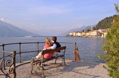 Couple of young tourists is sitting on a bench and observing beautiful panoramic view of lake Como at Bellagio. stock photo