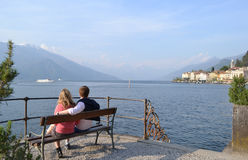Couple of young tourists sitting on bench and watching lake Como at Bellagio Stock Photography