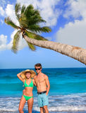 Couple of young tourists in a tropical beach Royalty Free Stock Photos
