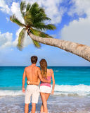 Couple of young tourists in a tropical beach Stock Images