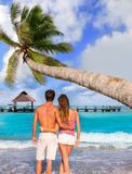 Couple of young tourists in a tropical beach Royalty Free Stock Images