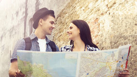 Couple of young travelers with map: walking around town. Stock Photography