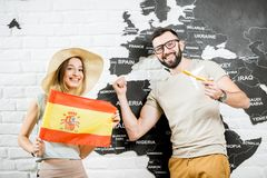 Young couple dreaming about a trip to Spain. Couple of young travelers standing with spanish flag near the wall with world map, dreaming about summer vacations Royalty Free Stock Photos