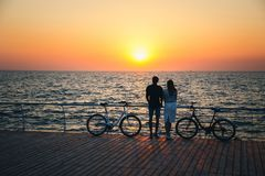 Couple of young travellers hugging at the beach and watching the sunrise at wooden deck with two bicycles near, summer time royalty free stock photography