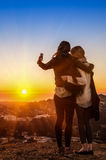 Couple of young women best friends taking a selfie during sunset Stock Photography