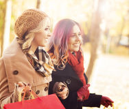 Couple of young women with shopping bags in the park Stock Images