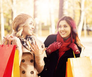 Couple of young women with shopping bags in the park Stock Image