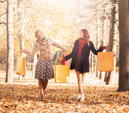 Couple of young women with shopping bags in the park Stock Photos