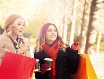 Couple of young women with shopping bags in the park Royalty Free Stock Photos