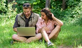 Couple youth spend leisure outdoors with laptop. Modern technologies give opportunity to be online and work in any. Environment conditions. Man and girl looking stock image