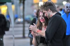 Couple with zombie face paint looking at their phone on the square ,Eire Square, Galway, Ireland September 2017 royalty free stock images