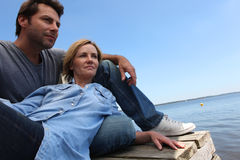 Coupleby the water. Couple lazing by the water stock photo