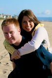 Couplel In Love. Couple in love on beach hugging and looking at the camera Royalty Free Stock Photography