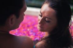 Couplere laxing bad med tropiska blommor som är utomhus- på det lyxiga hotellet arkivfoto