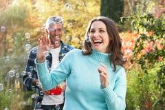 Couples à l'extérieur avec la machine de bulle Photos libres de droits