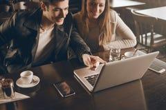 Couples à la barre utilisant un ordinateur portable Photographie stock