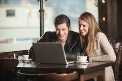 Couples à la barre utilisant un ordinateur portable Photographie stock libre de droits