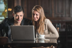 Couples à la barre utilisant un ordinateur portable Photos libres de droits