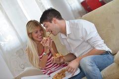 Couples à la maison mangeant de la pizza Photographie stock