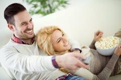 Couples à la maison regardant la TV Photos libres de droits