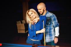 Couples à la mode ayant le billard d'amusement et de jeux Image libre de droits