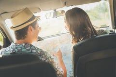 Couples à la mode dans l'intérieur de voiture utilisant la carte sur la promenade en voiture pour des directions Photo stock