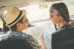 Couples à la mode dans l'intérieur de voiture utilisant la carte sur la promenade en voiture pour des directions Photos libres de droits