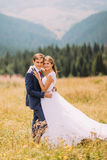Couples à la mode et heureux de mariage étreignant sur le champ ensoleillé avec le fond de forêt Images stock