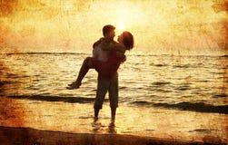 Couples à la plage dans le coucher du soleil. Photographie stock