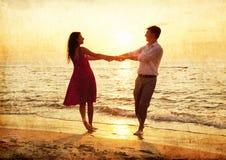 Couples à la plage dans le coucher du soleil. Images libres de droits