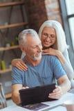 Couples âgés aimants utilisant le comprimé à la maison Image stock